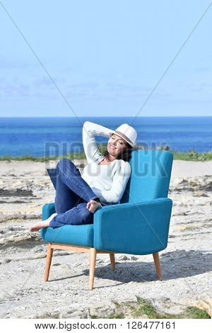 Woman in armchair relaxing on a cliff by the sea