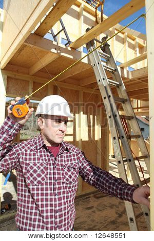Laborer working on a house under construction