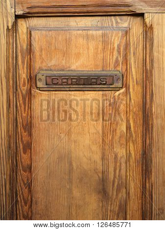 Old wooden door with a metallic mailbox