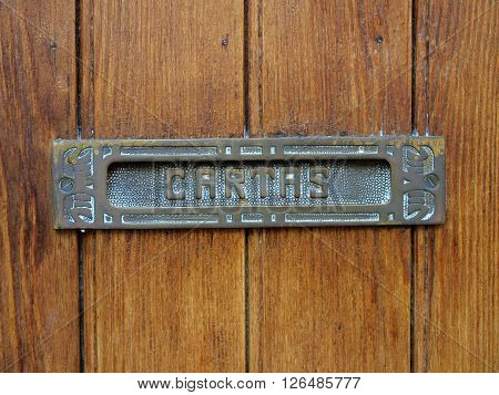 Detail of an old wooden door and a metallic mailbox on it