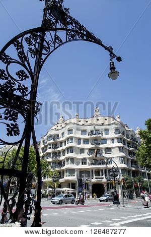 SPAIN, BARCELONA, JUNE, 27, 2015 - Black openwork weaving a street light on the background famous house of Antonio Gaudi Casa Mila or La Pedrera in Barcelona, Catalonia, Spain.