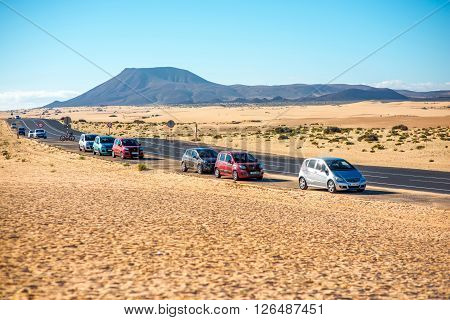 CORRALEJO, FUERTEVENTURA ISLAND, SPAIN - SIRCA JANUARY 2016: Road with cars on Corralejo desert on Fuerteventura island