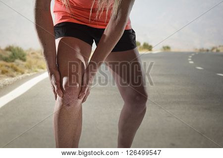young sport woman with strong athletic legs holding knee with his hands in pain after suffering ligament injury during a running workout training on asphalt road background