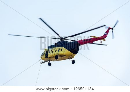 Tyumen, Russia - August 11, 2012: UTair airshow in Plehanovo heliport. Descent of empty stretcher from MI-8 helicopter by rope