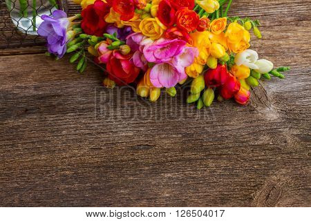 Fresh freesia flowers posy on wooden table  background with copy space