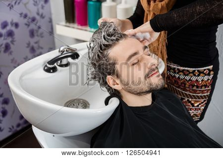 Beautician Washing Male Client's Hair In Salon poster