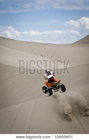 ATV rider jumping sand dunes