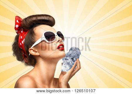 The vintage photo of a glamorous vintage pin-up girl holding a cool ice cube on her skin for rejuvenation on colorful abstract cartoon style background.