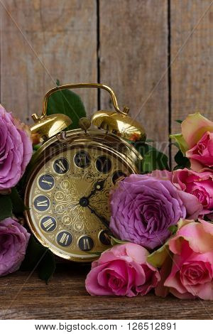 bouquet of pink and violet  fresh roses with vintage alarm clock