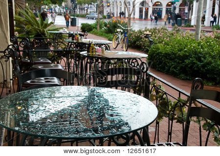 Wrought Iron Chairs And Glass Top Table Setting At Sidewalk Café In Santa Barbara, Ca.