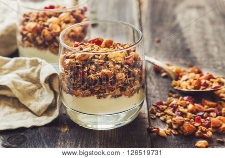 Homemade granola muesli with nuts and dried cranberries and yogurt in glasses on rustic wooden background. Healthy breakfast.