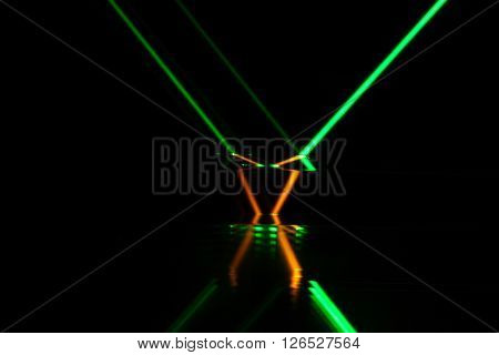 A green laser beam reflection in different colored glass.