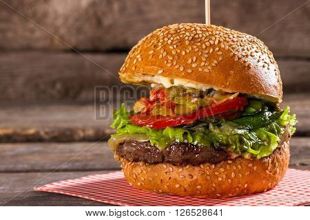 Burger with tomatoes on stick. Freshly cooked hamburger on table. Juicy beef and fresh tomatoes. All the needed ingredients.