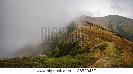 Hiking Trail on the Hill with Fog in the Mountains on Overcast Day