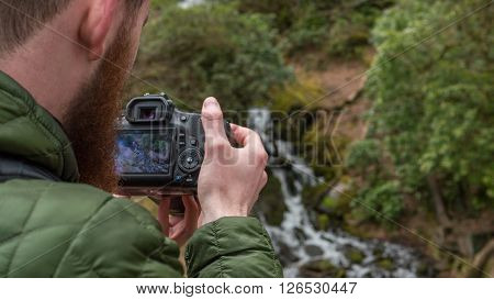 A photographer takes a picture of a waterfall in Cornwall, England