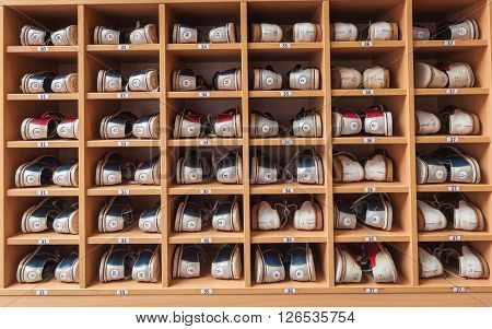 Bowling shoes in a shoe cabinet sorted by size