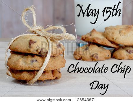 Close up of chocolate chip cookies tied with twine in front of a glass of milk and other cookies on wood background. Message for International Chocolate Chip day on May 15th.
