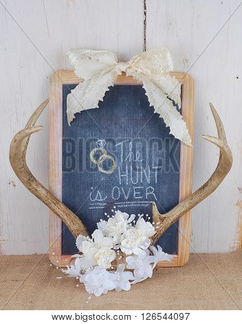 Rustic wedding image with antlers and silk flowers and ribbons framing a worn blackboard with the phrase the hunt is over. Good for