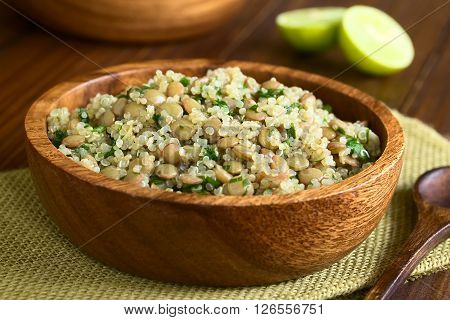 Quinoa salad with lentils and parsley in wooden bowl photographed on dark wood with natural light (Selective Focus Focus one third into the salad)