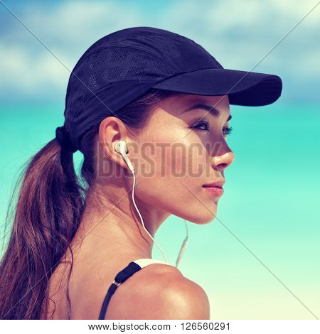 Fitness runner woman listening to music on beach. Portrait of beautiful girl wearing earphones earbuds and running cap for sun protection. Asian woman healthy and active in summer.