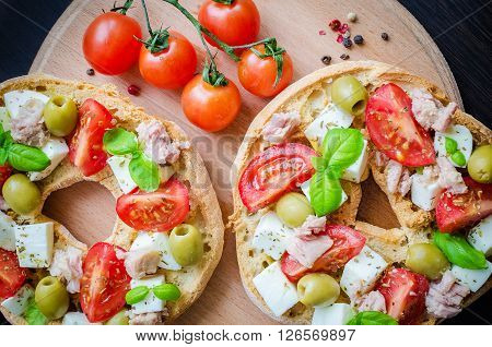 Classical frisella tomato, cheese mozzarella, tuna and olives. Italian starter friselle. Dried bread called freselle on wooden board with tomatoes cherry. Italian food. Healthy vegetarian food. poster