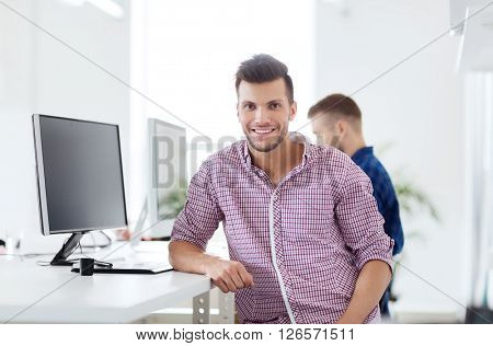 business, technology, education and people concept - happy young creative man or student with computer at office