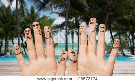 gesture, family, wedding, people and body parts concept - close up of two hands showing fingers with smiley faces over exotic tropical beach with palm trees and swimming pool background