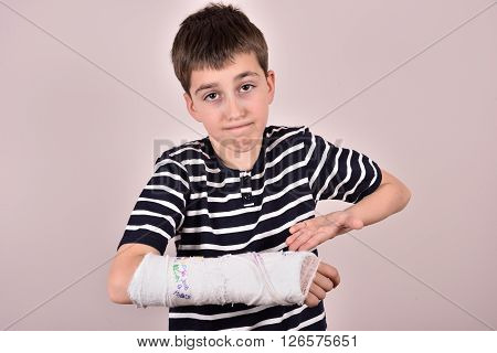 Young boy making a grimace and showing his broken arm with plaster that has been autographed by friends
