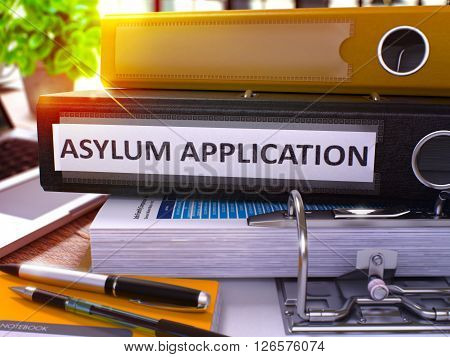 Black Ring Binder with Inscription Asylum Application on Background of Working Table with Office Supplies and Laptop. Asylum Application Business Concept on Blurred Background. 3D Render.
