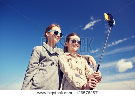 people, children, friends and friendsip concept - happy girls taking picture with smartphone on selfie stick outdoors