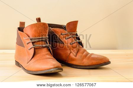 Still life with Brown leather shoes with wooden shoe stretchers on wooden table with clipping path