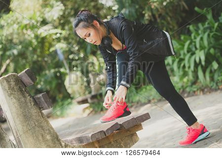 Asian Woman Tying Her Shoes, Prepared For Jogging