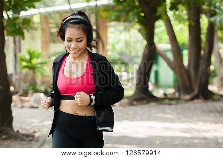 Asian Woman Jogger Listening To Music And Running In The Outdoor Park. Female Fitness Model