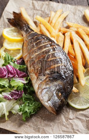 Grilled gilt-head bream fish with salad and french fries