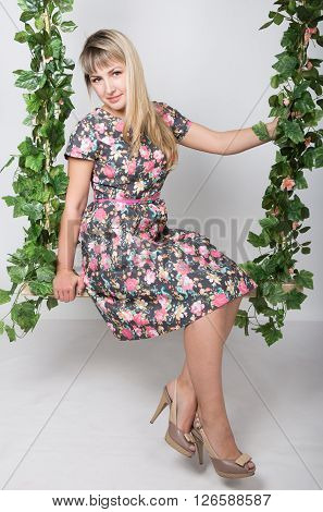 Beautiful young leggy redhaired woman in a long colorful dress on a swing, wooden swing suspended from a rope hemp, rope wrapped vine and ivy.