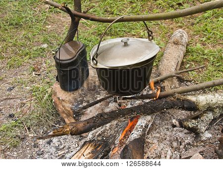 pots on a fire in the forest sunny summer day