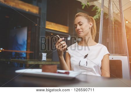 Charming European female browsing wifi via mobile phone during morning breakfast in cafe bar beautiful woman reading text message on her cell telephone while sitting in coffee shop during free time