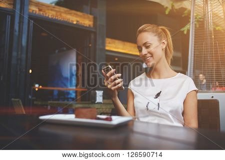 Young happy female reading good news on her mobile phone while sitting in modern coffee shop interior gorgeous hipster girl with beautiful smile watching funny video on cell telephone during lunch