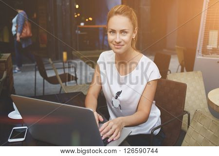 Portrait of a beautiful lady sitting at the table of sidewalk cafe with open laptop computer young charming female posing during work on her portable net-book pretty Caucasian woman using technology