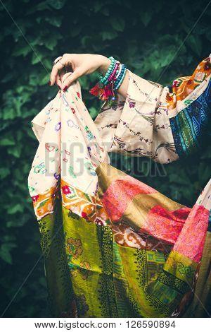 summer boho silky dress with woman hand hold it outdoor shot in garden closeup