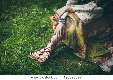 woman legs  on grass in strap flat sandals and boho style silky  dress  with lot of bracelets on hands