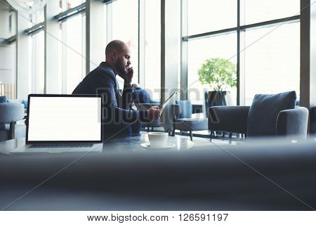 Man entrepreneur is looking on touch pad a bad figure income last month and listening via a mobile phone to the explanation of the subordinate while is sitting near net-book with copy space screen poster