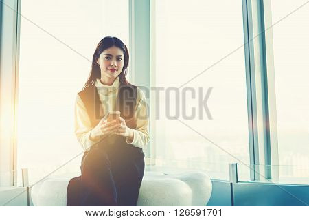 Young Asian woman with trendy look is using her cell phone for on-line ordering while is sitting in her luxury apartment. Gorgeous hipster girl with mobile phone in hands is posing for camera