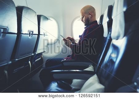Man is listening to music in headphones and chatting in social network via mobile phone during his flying in an airplane. Hipster guy is watching video on cell telephone while is sitting in plane