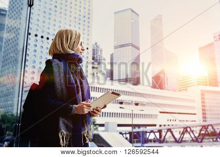 Young hipster girl is holding digital tablet and looking in window at active life of big metropolitan city with tall skyscrapersbackground with copy space for your advertising text message or content