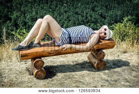 Young caucasian woman with sunhat in sailor outfit is lying on the wooden bench. Beauty and fashion.