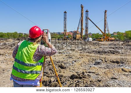 Woman surveying is measuring level on construction site. Surveyors ensure precise measurements before undertaking large construction projects.