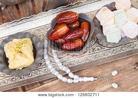 Turkish delights with tasbih on silver oriental tray, top view poster