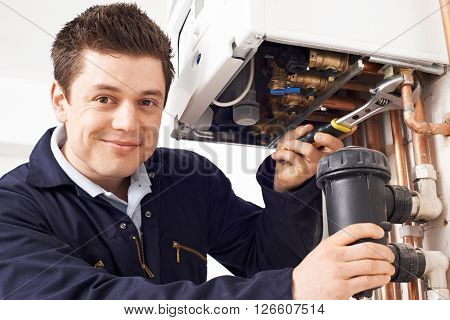 Male Plumber Working On Central Heating Boiler poster