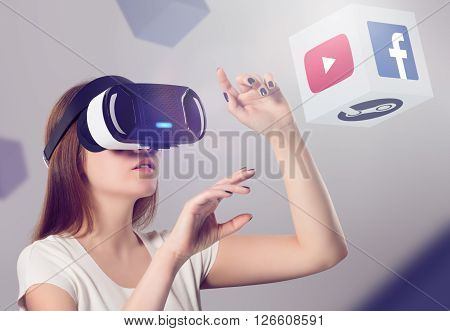 Varna Bulgaria - March 10 2016: Woman in VR headset looking up and interacting with Facebook Youtube Steam VR content. Facebook Google & Steam believes that VR is the future of content consumption.